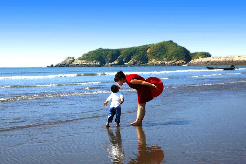 年轻的母亲领着孩子在海滩上漫步,追逐海浪,人与自然合谐相处,看着也是醉了。
